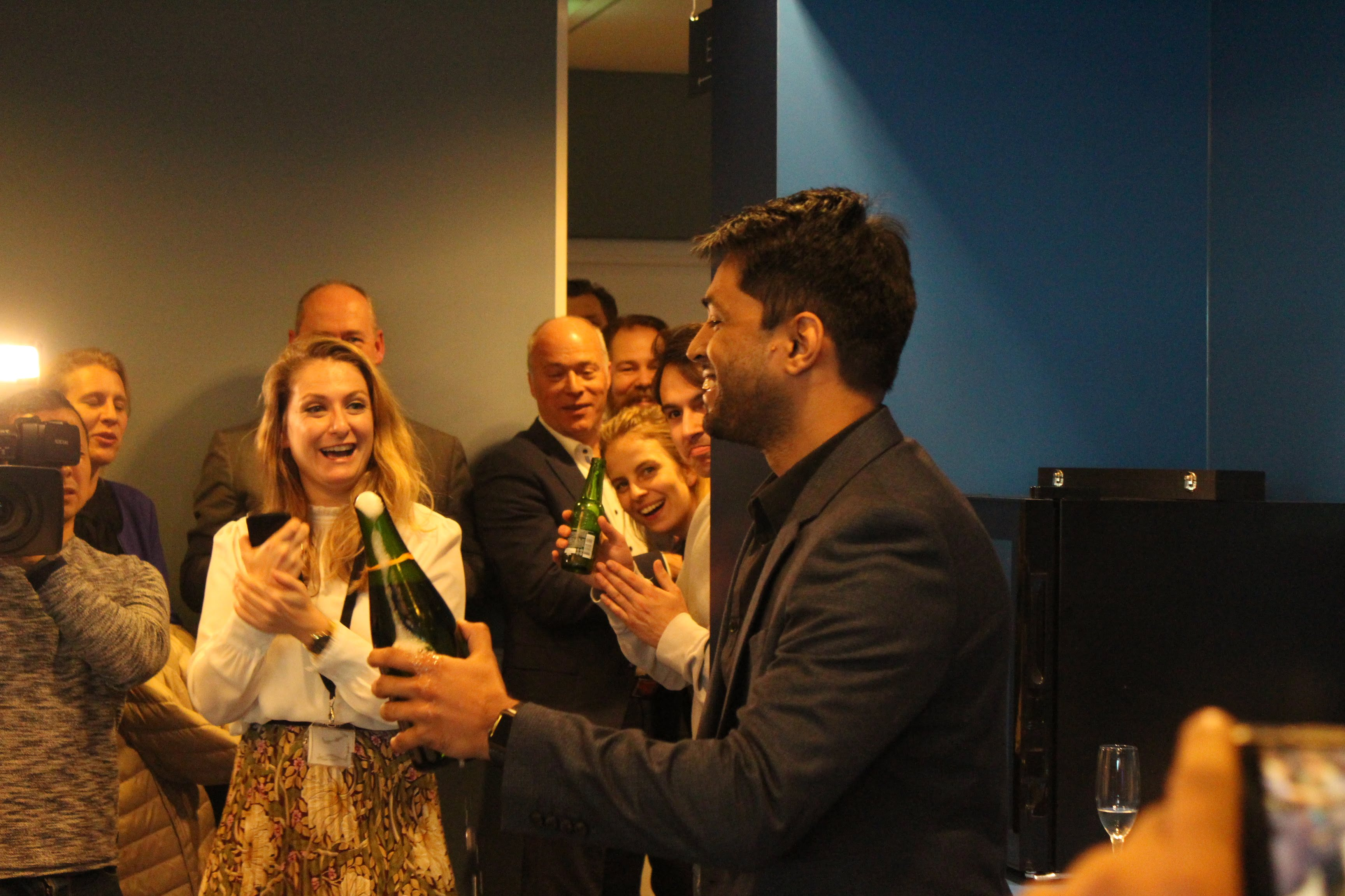 Co-founder Karthik Mahadevan holds the open champagne bottle and smiles.
