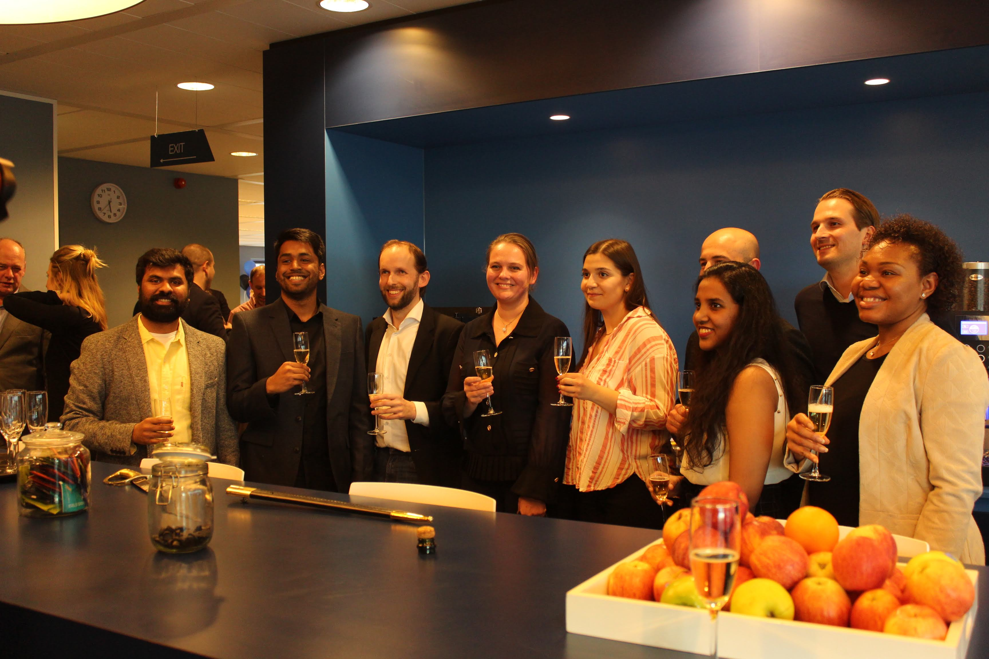 The entire Envision team and 4impact team pose together for a picture, each holding a champagne glass and smiling