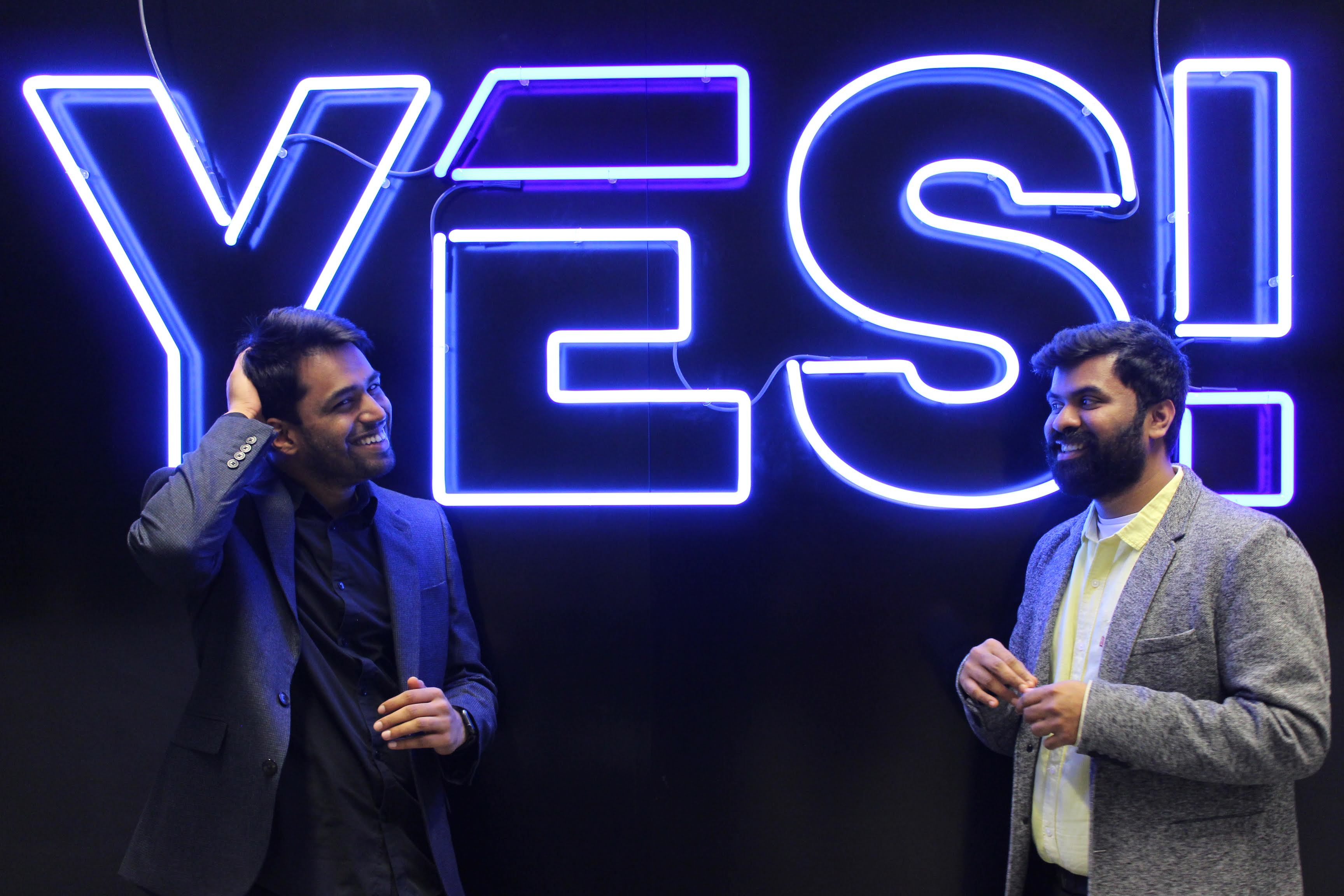 Founders Karthik Mahadevan and Karthik Kannan smile while posing in front of a big blue neon sign which reads YES!, the logo of Envision's hub.