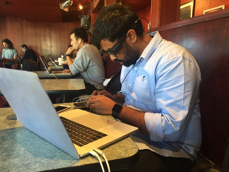 Co-founder Karthik Kannan is sitting at a cafe, wearing the prototype glasses while he works on his laptop and smartphone.