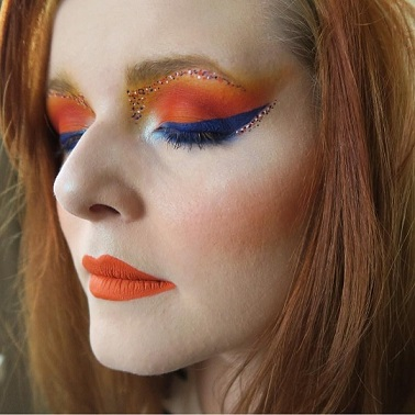 A photo of Lucy Edwards, with orange and blue glittery make-up.