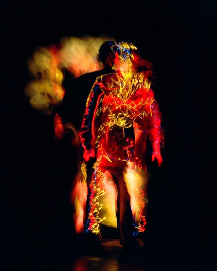 The figure of a man is seen on a black background. The man is covered in wiggly yellow, red and some blue colours.