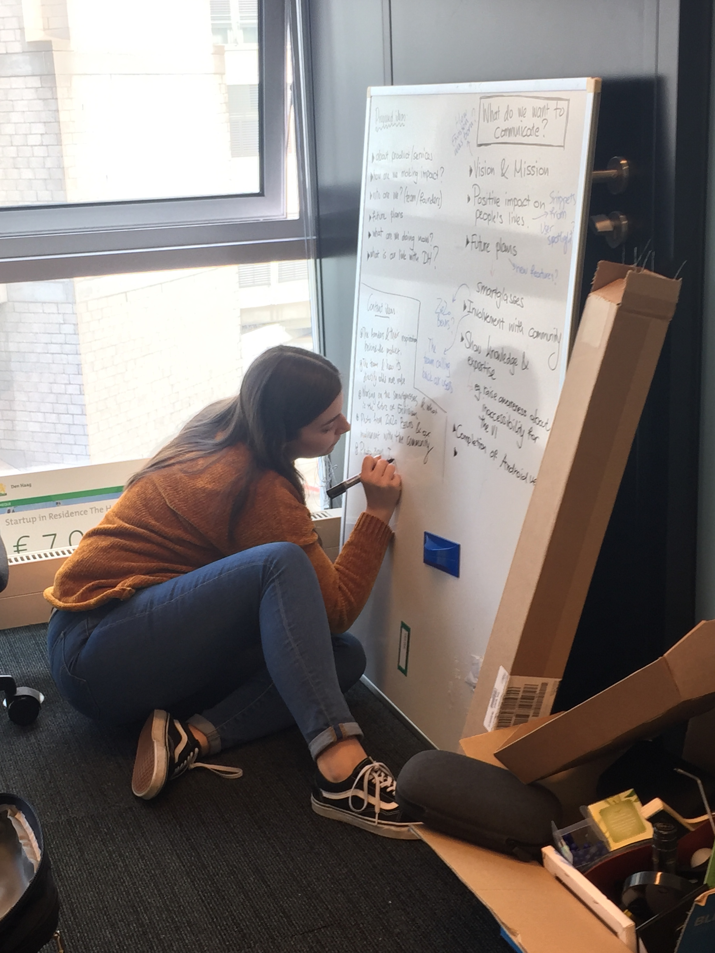Picture of Dafni sitting on the floor of our new office and writing marketing plans on a white board