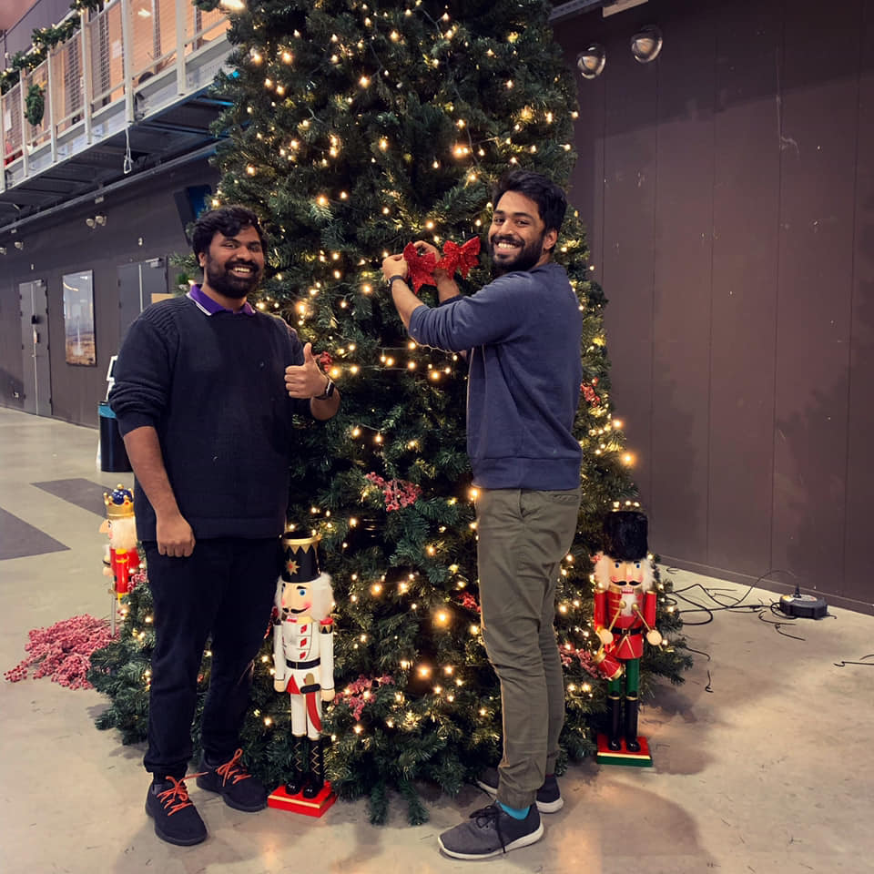 Karthik and Karthik posing for the camera while decorating a christmas tree.