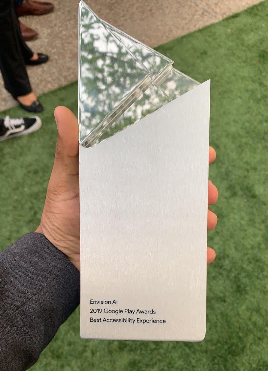 Karthik Kannan holding the Google Play Award in his hand with Envision AI etched on it.