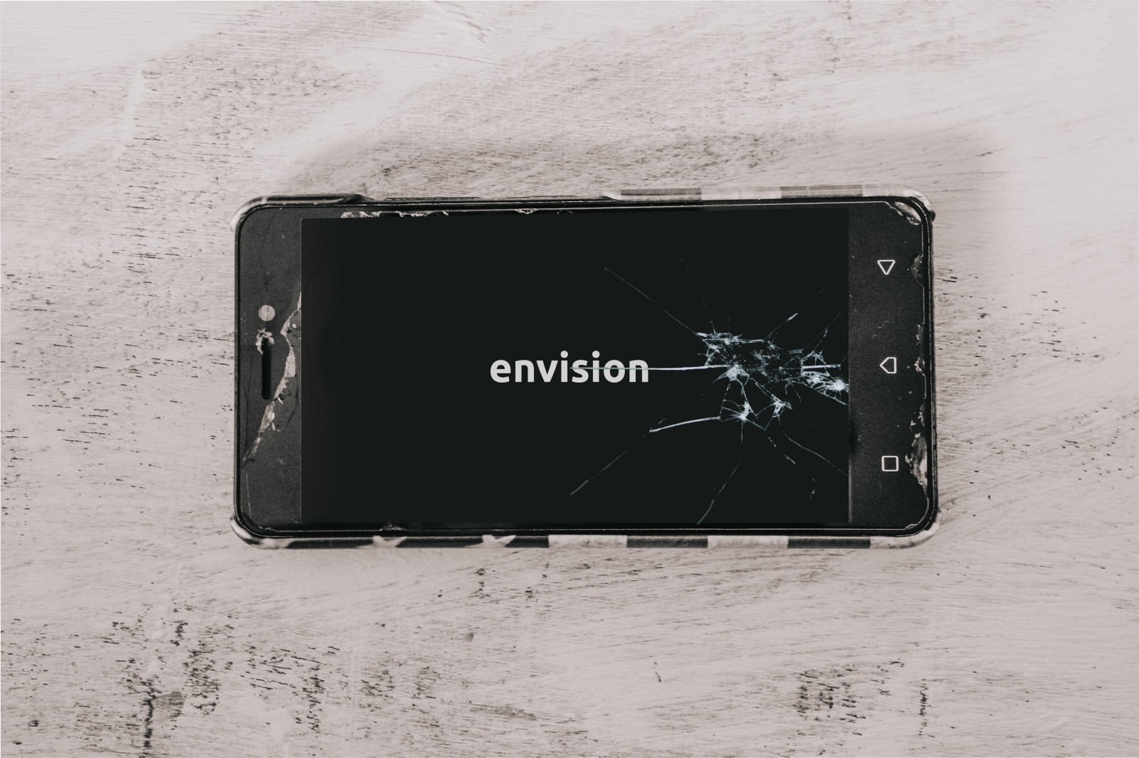 "A picture of a smartphone on a table with multiple cracks on it with the text on screen reading ""Envision"""