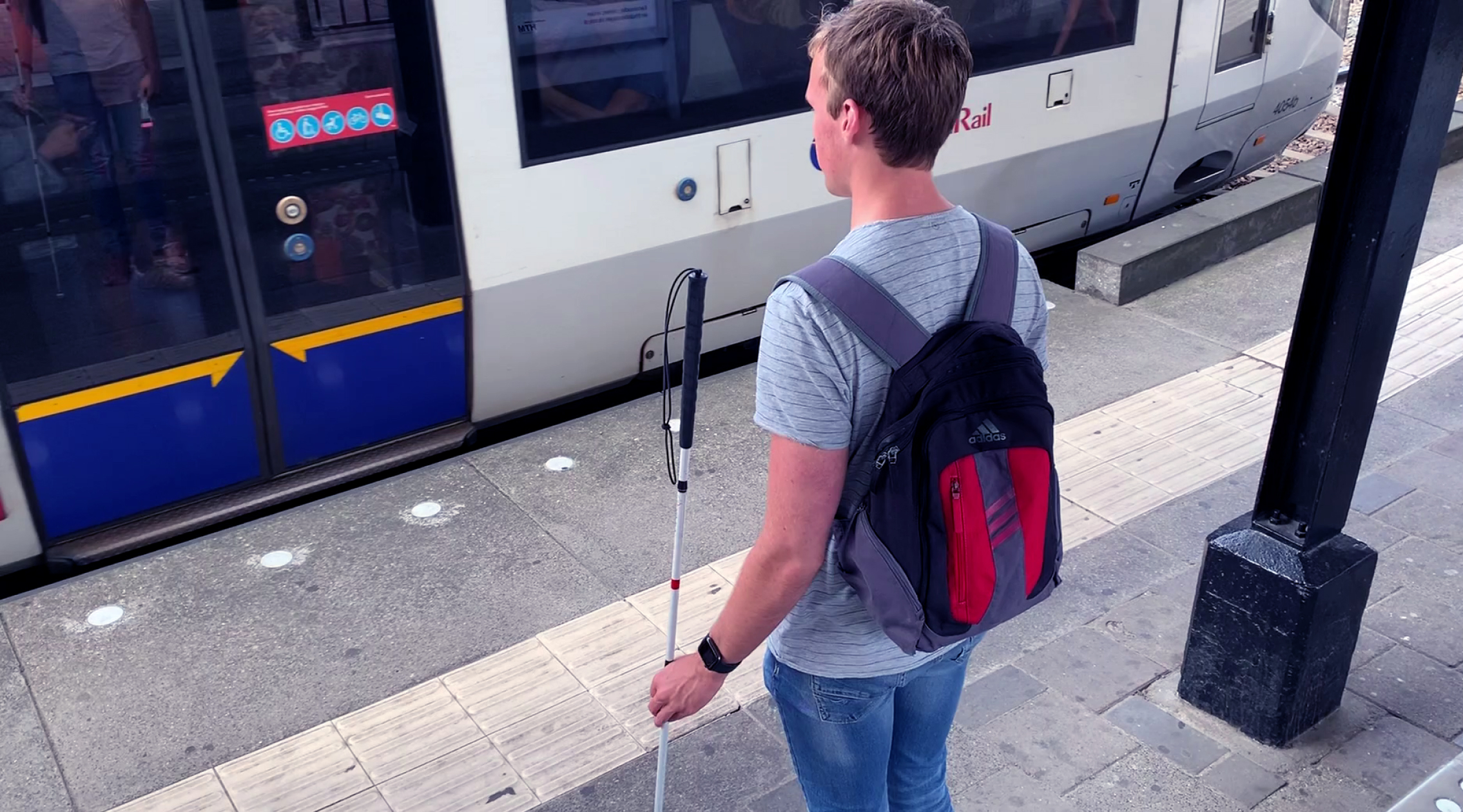 Jesse standing in front of a train at the station holding a cane.