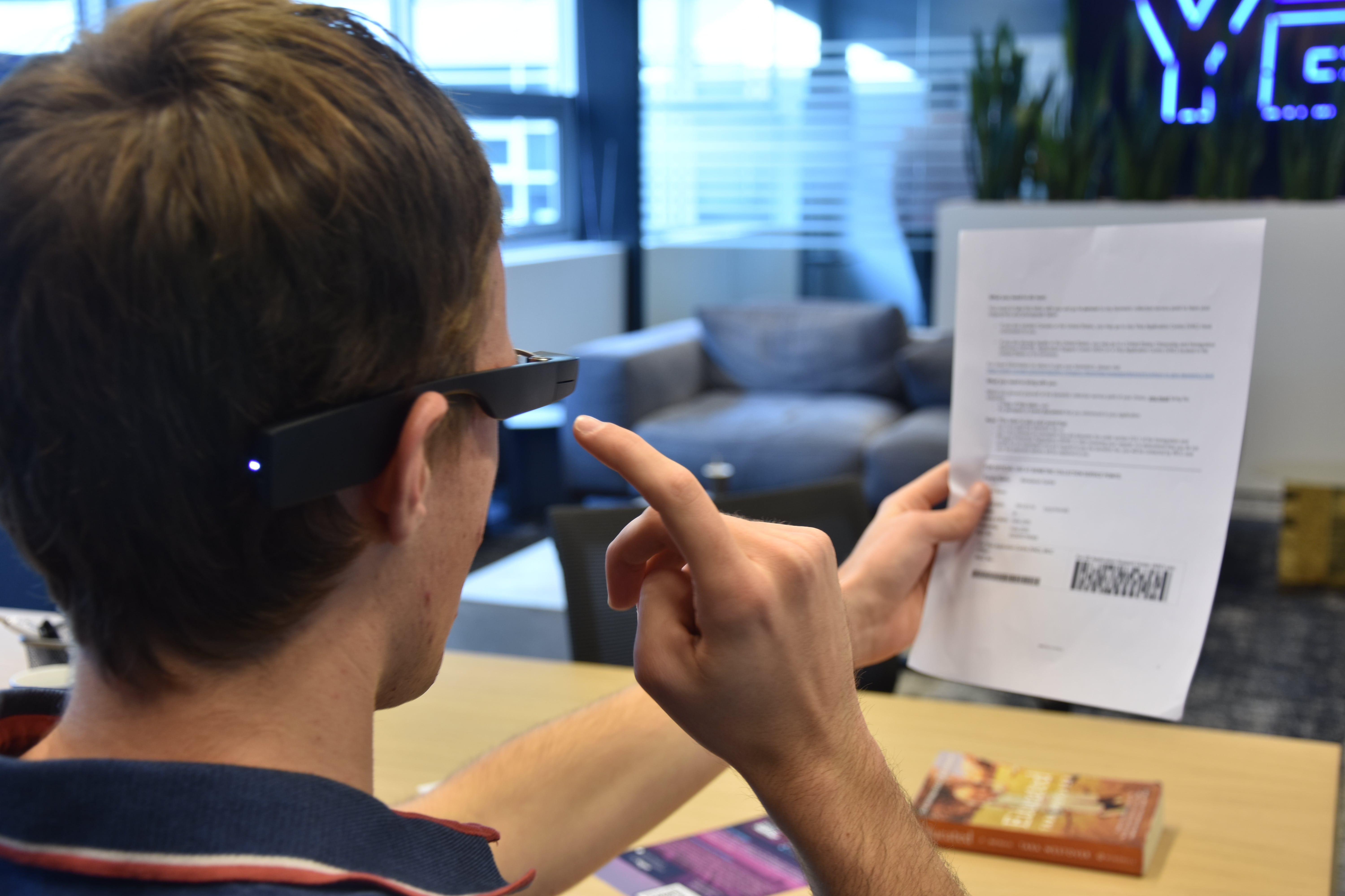 A user reading a document in his hand by tapping the touchpad of the Google Glass