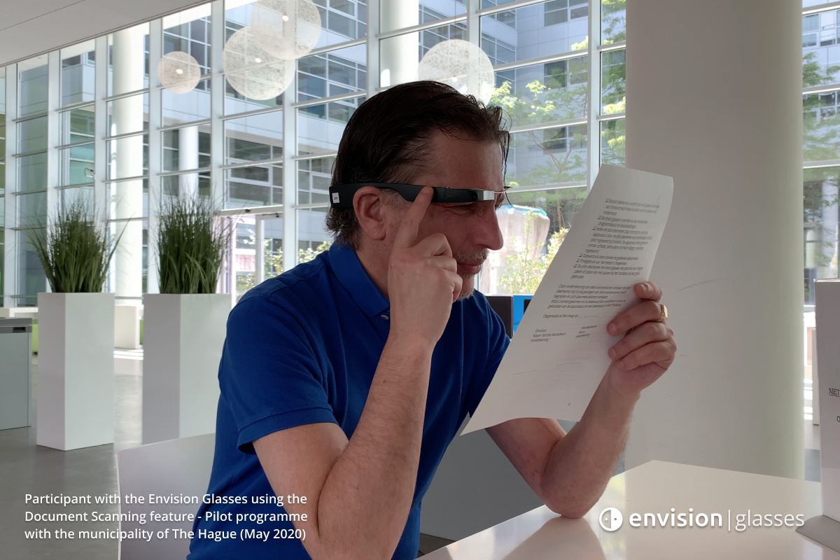 A participant of the pilot programme using the document scanning feature of the Envision Glasses while holding tapping with his right finger on the Envision Glasses and holding a document with his left hand.