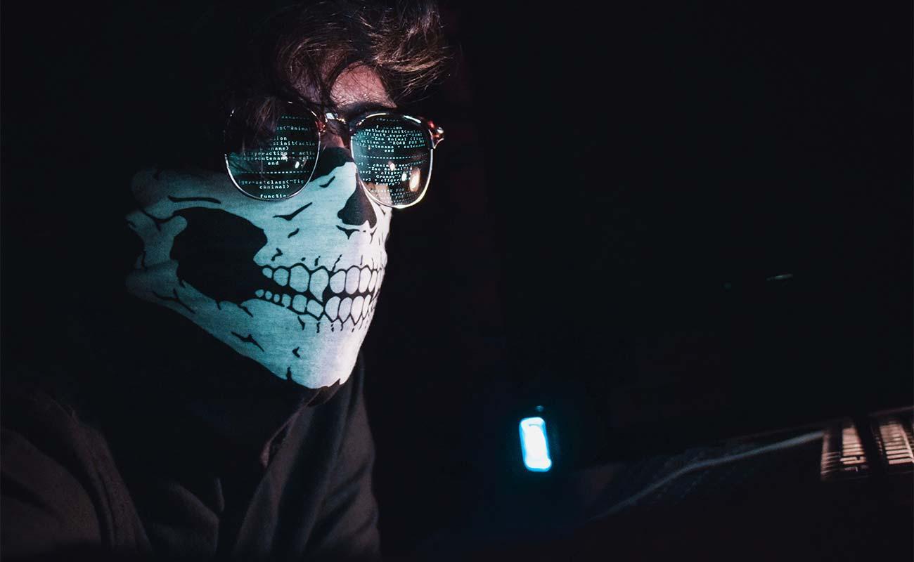 Mann vor Computer mit Maske & Sonnenbrille