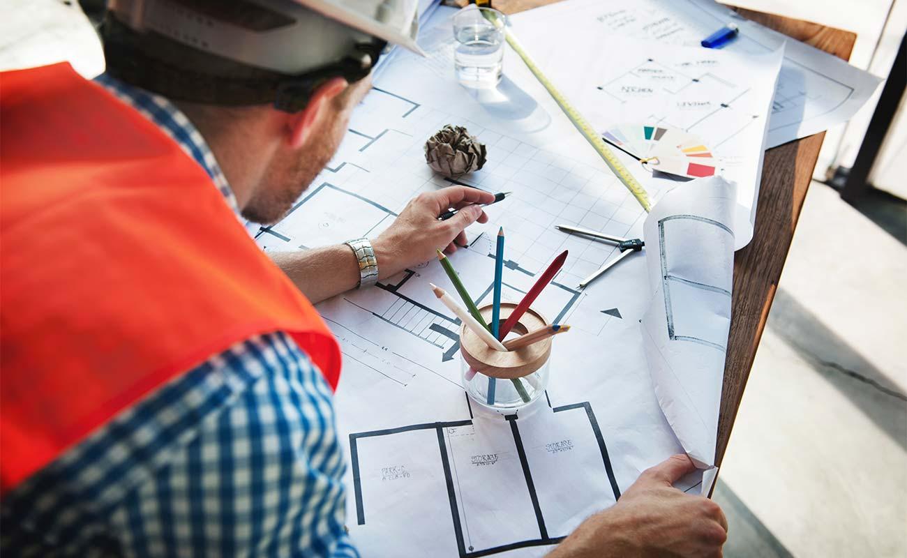 Architekt betrachtet mehrere Baupläne