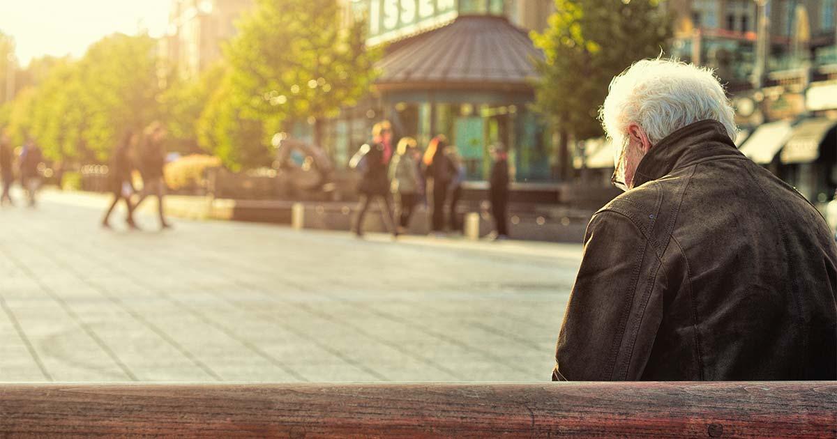 Älterer Mann sitzt auf einer Bank