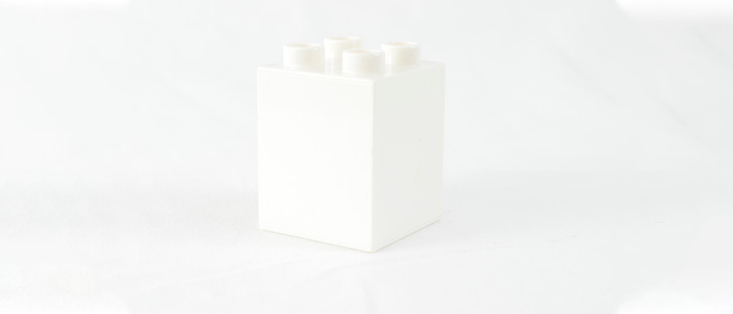 a white lego brick on a white background - showing that everyone starts from a blank canvas