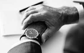 Black and white image of a man checking his watch