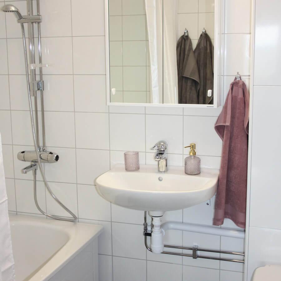 Badrum med spegelskåp, handfat och badkar. Vitt kakel på vägg. Dekorativa detaljer med rosa handduk, ljushållare och tvålpump.
