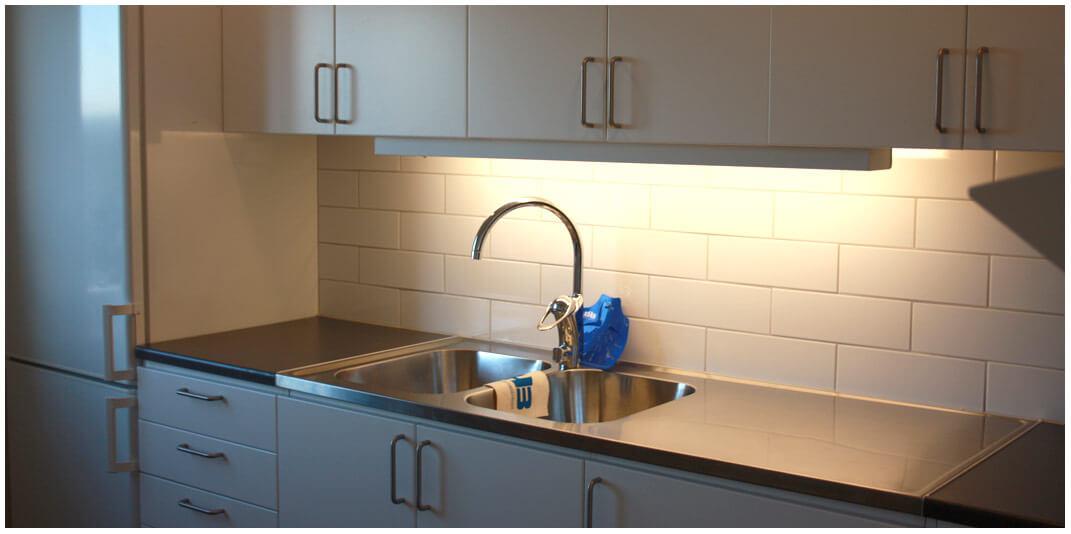 Kök med vita luckor, två rostfria diskhoar och grå bänkskiva.