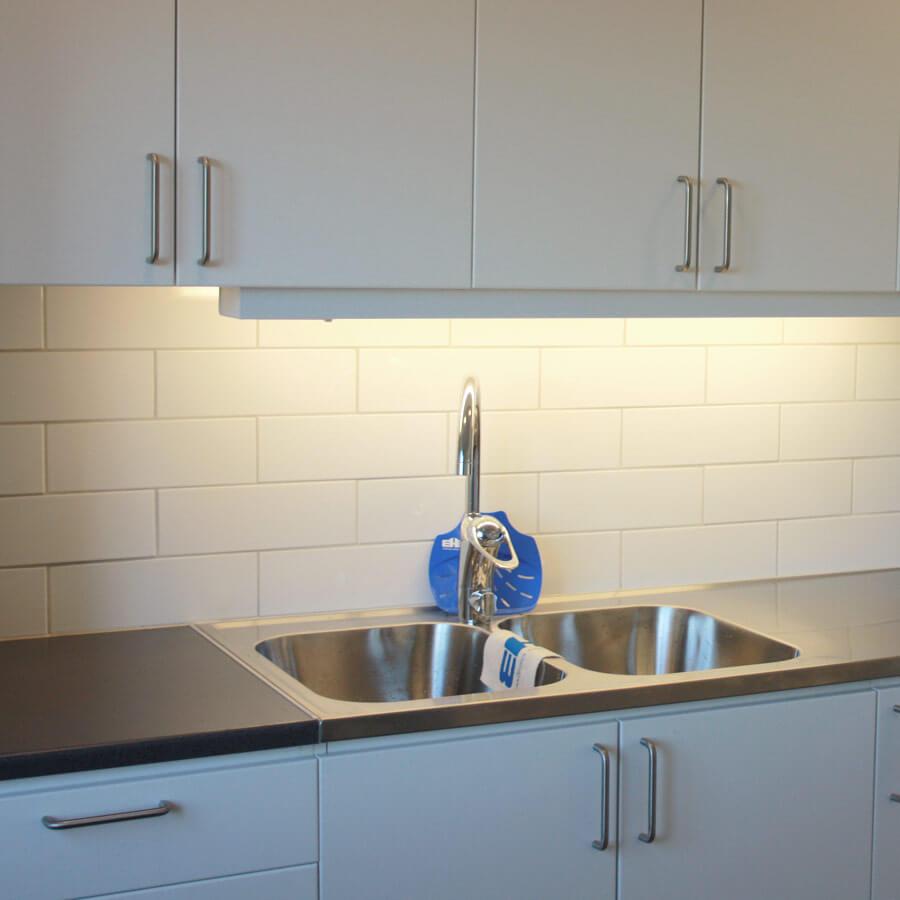 Kök med vita luckor, två rostfria diskhoar och grå bänkskiva. Vitt kakel som stänkskydd.