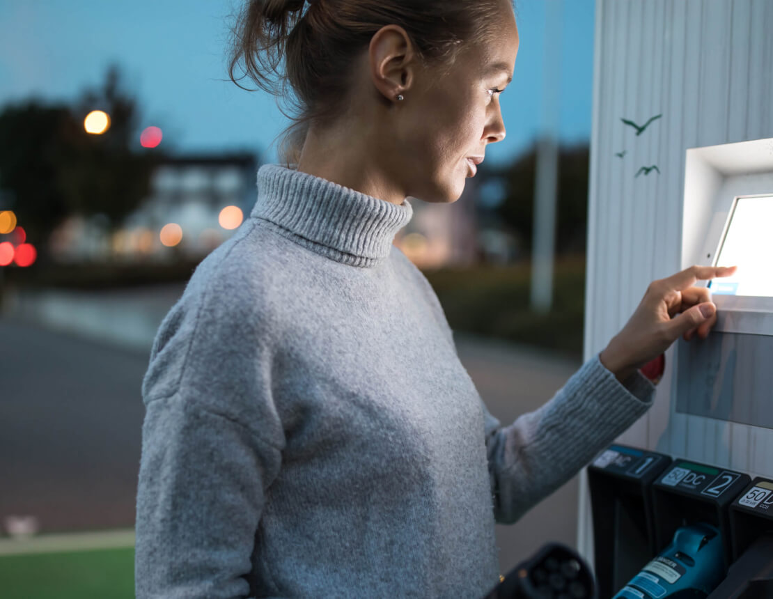 woman operating EV charger