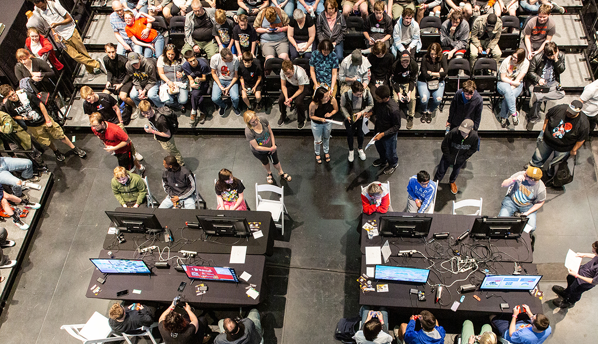 A picture taken from above shows an audience of at least 50 people watching two gaming stations in the middle of the room.