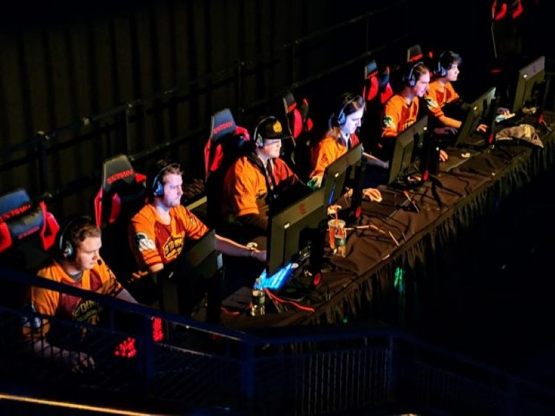 A team of professional esports players sit at their computers during a tournament