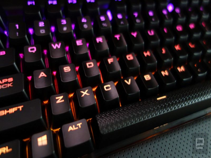 The keyboard of a gaming computer, backlit with purple and orange light