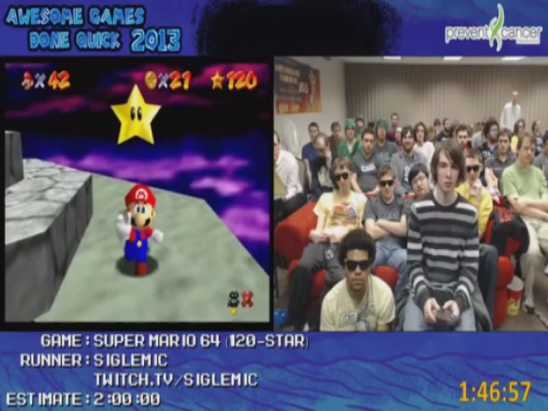 a split screen showing a super mario run on the left and a room full of people sitting behind a speedrurner on the right