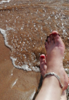 feet in waves on beach. (c) Therapy Room Annan