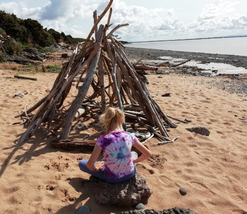 Child sitting on beach in front of driftwood den. (c) Therapy Room Annan