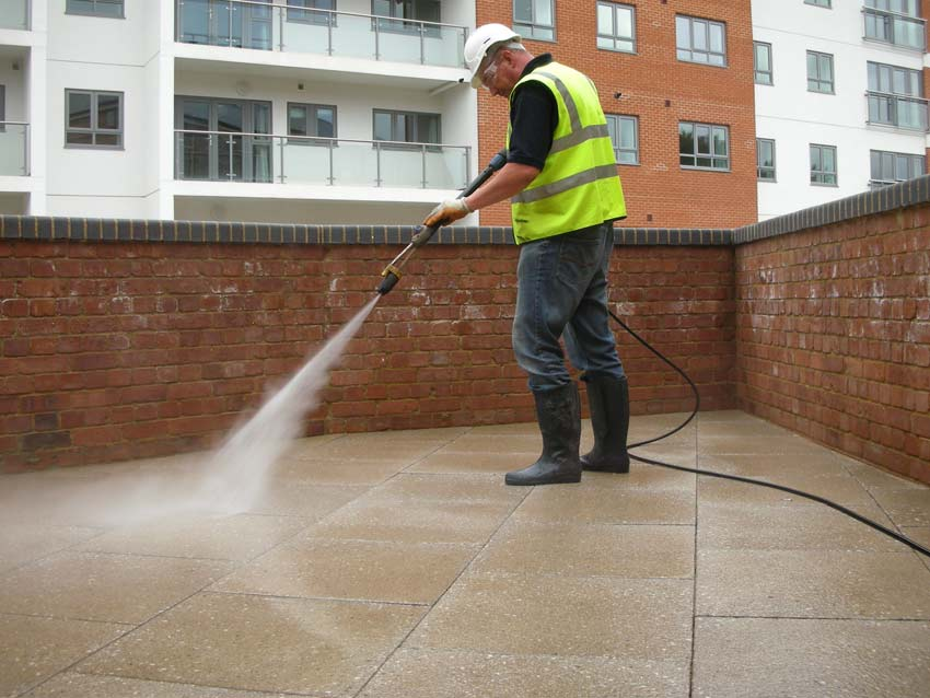 A man post construction cleaning using a power washer