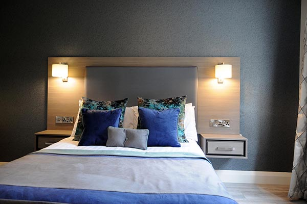 A double bed with blue pillows in Barr na Sraide's double room B&B accommodation in Dingle Ireland