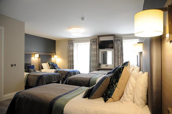 Three single beds and one double bed in a 5 Bed Family Room at Barr na Sraide's family hotel accommodation in Dingle Ireland