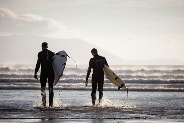 Two surfers at a stag party walking into the water near Dingle as recommended by Barr na Sraide Inn