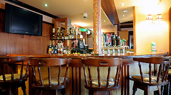 The bar at Barr na Sraide, with comfy seating in red and white and a blazing fire