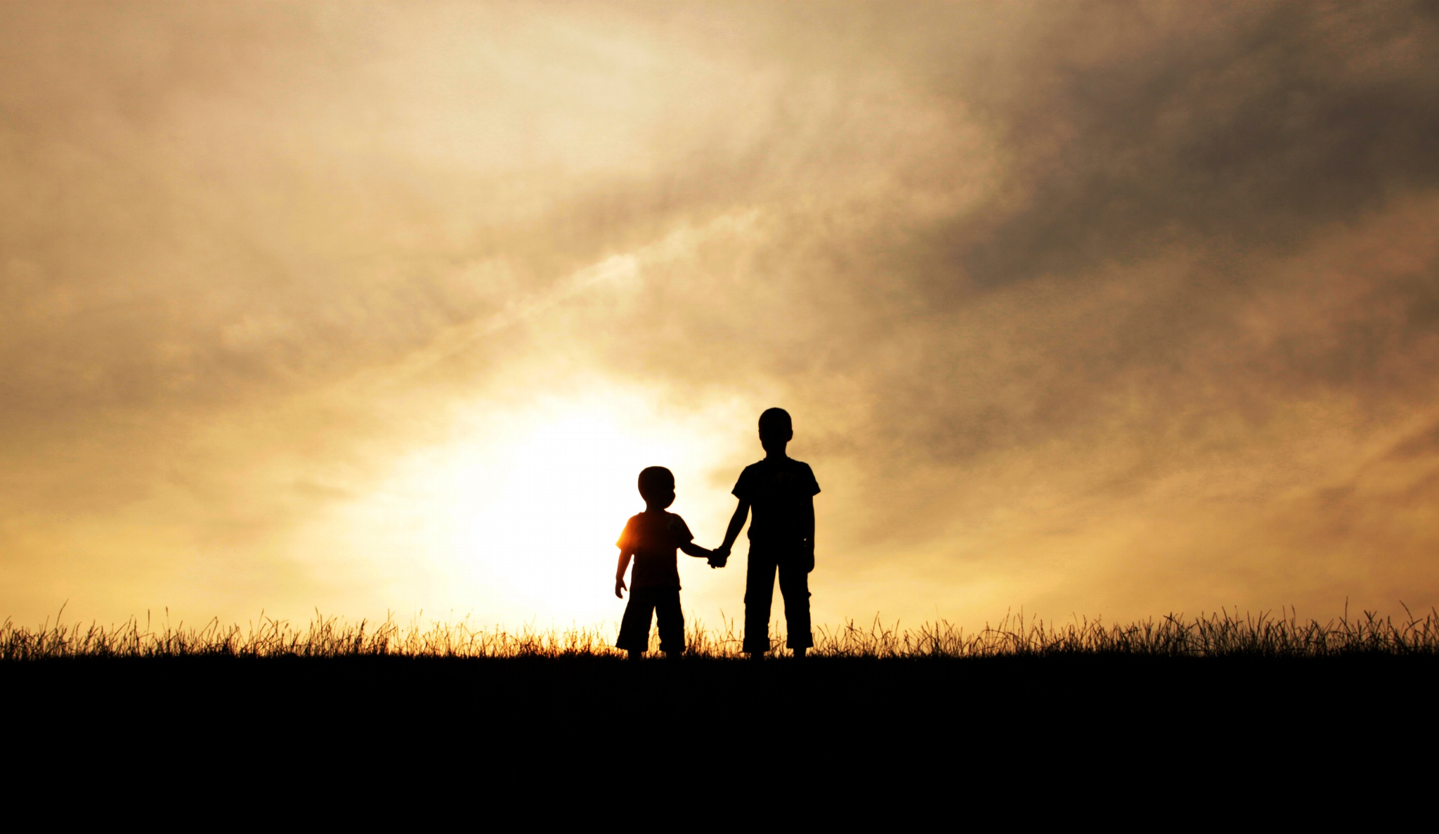 Ảnh hai đứa trẻ nắm tay nhau đón hoàng hôn
