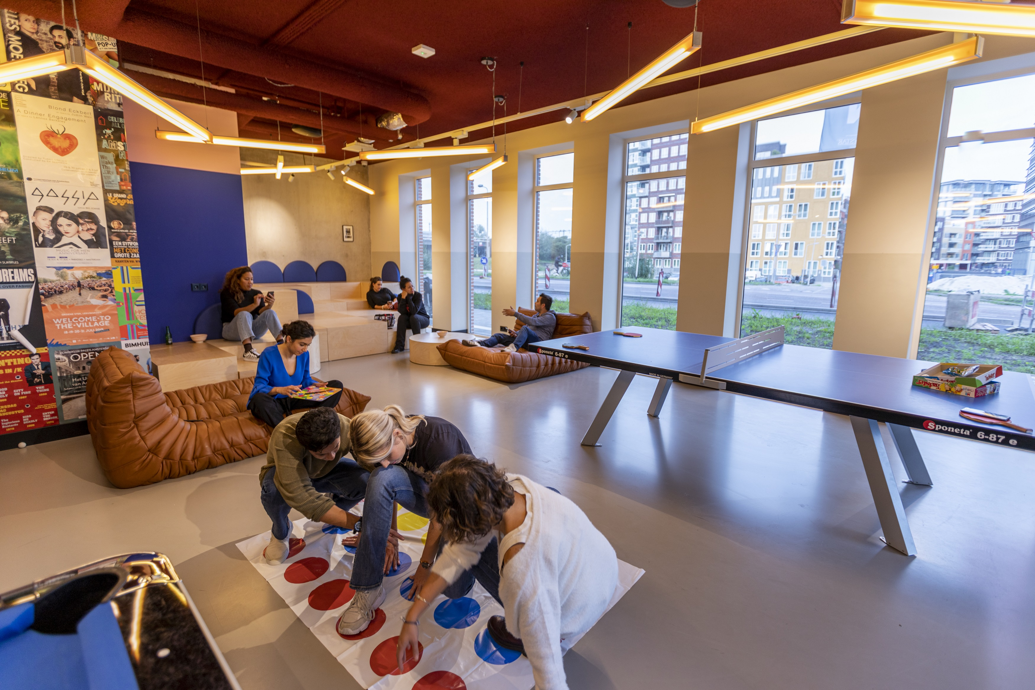 Residents playing twister in the game room of OurDomain Amsterdam Diemen