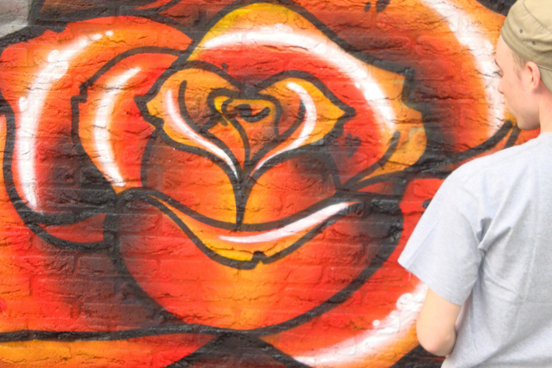 Man in front of a rose graffiti