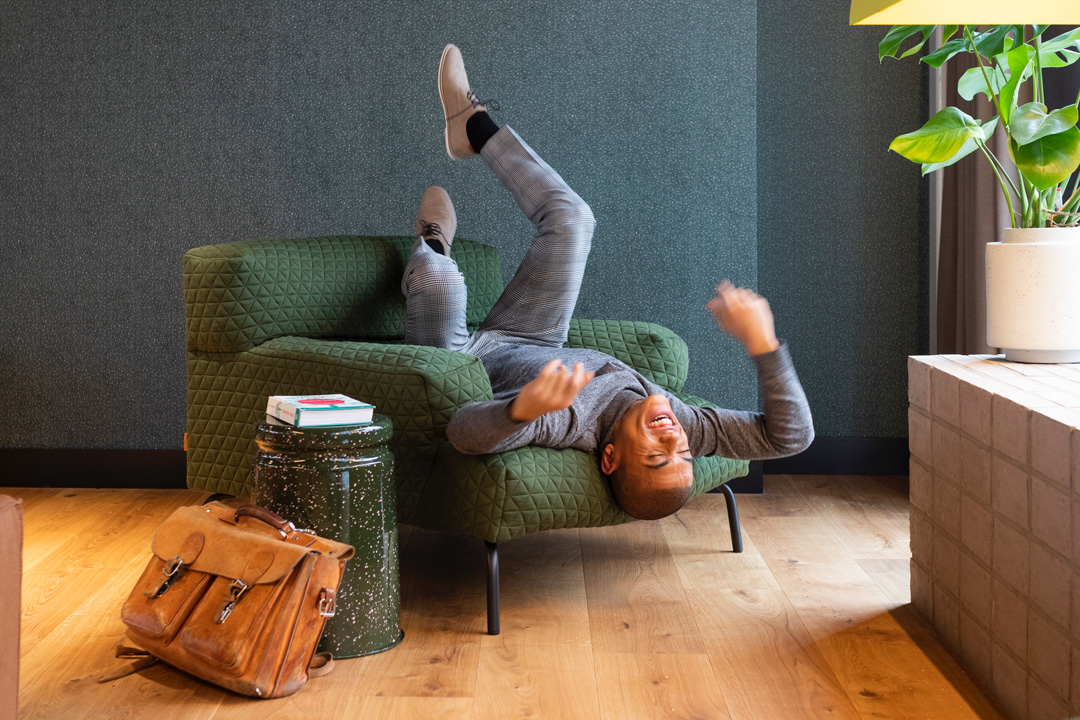 Guy sitting on an armchair upside down
