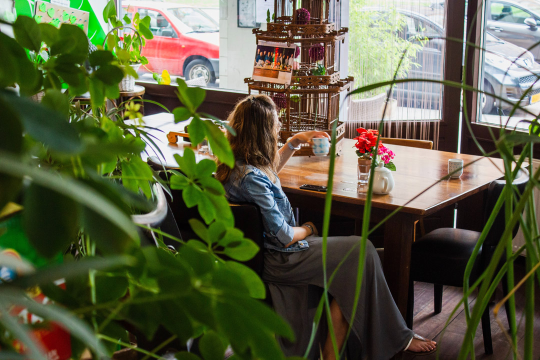 girl behind plants in a table at OurDomain Amsterdam South East