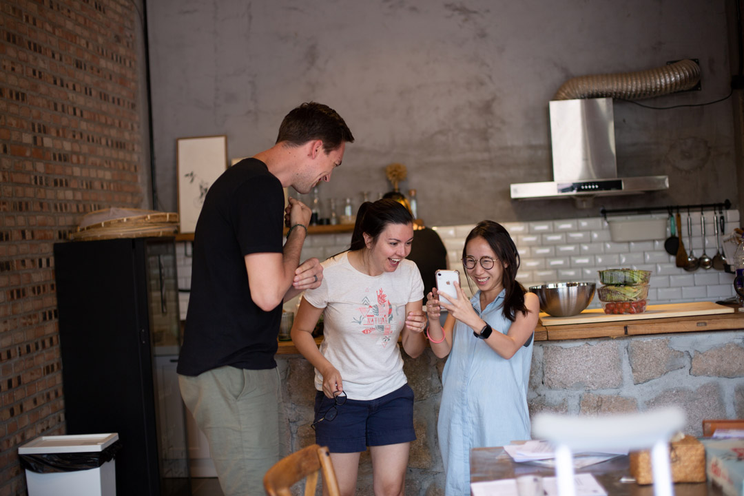 three friends standing and looking at a mobile phone while laughing inside of a restaurant