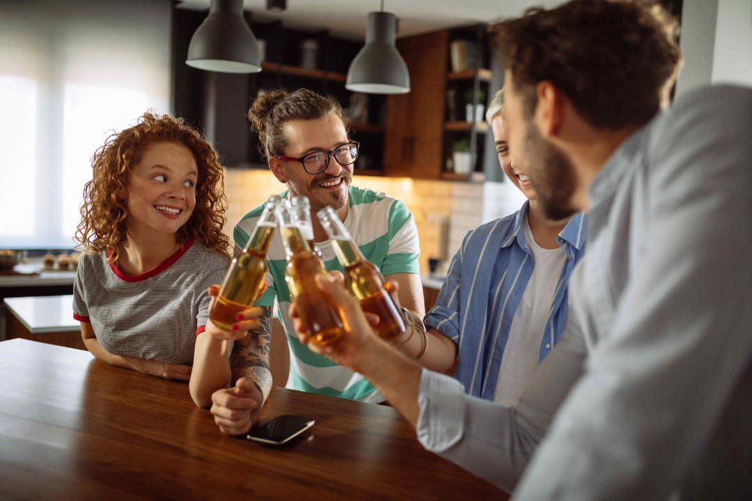 group of friends on a table cheering with beers
