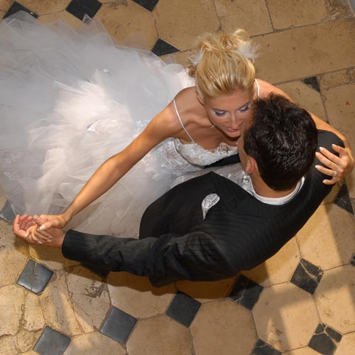 newly wedded couple dancing to the sounds of the wedding dj on a tiled floor