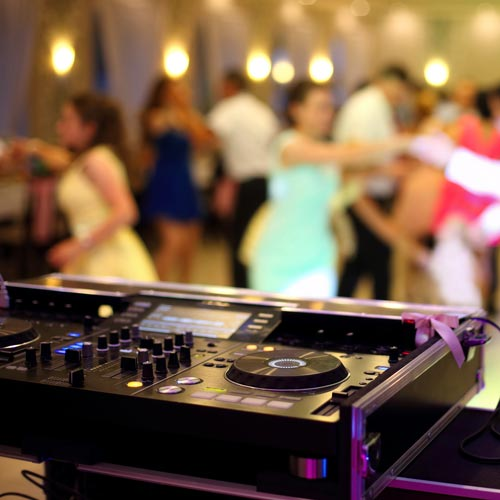 people dancing in front of the wedding dj console