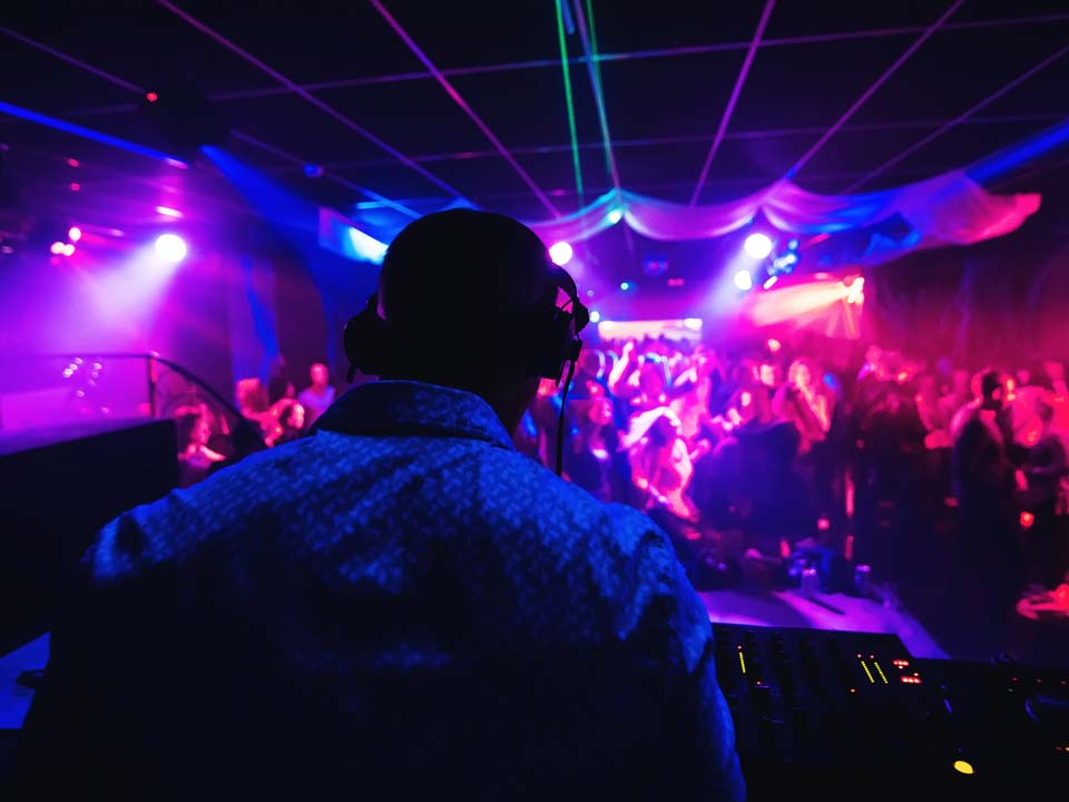behind a party DJ for hire in a nightclub setting