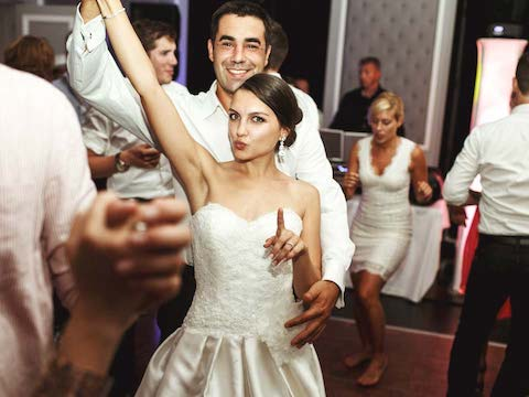a happy couple and group of people dancing to the music of the wedding dj