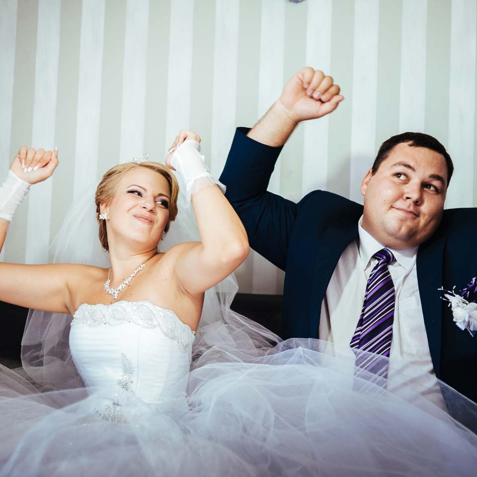 couple with hands in the air dancing to music played by a wedding DJ