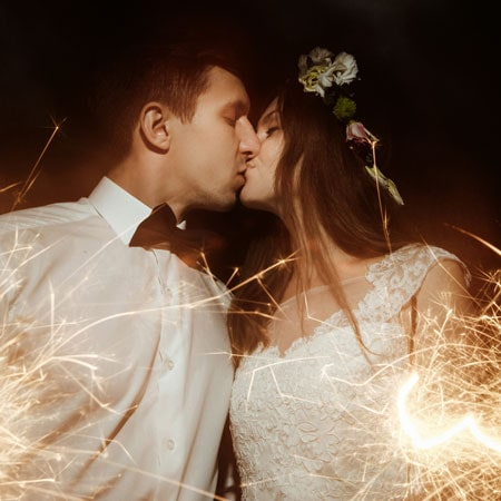 bride and groom having a kiss and holding some sparklers