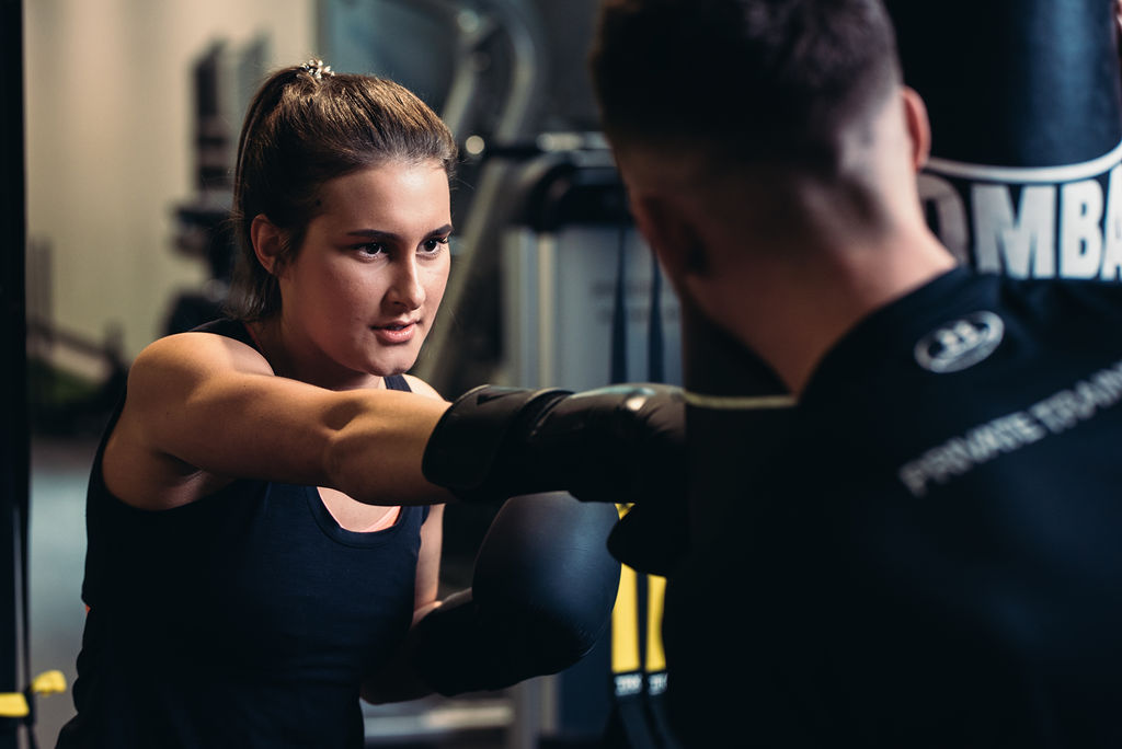 A young woman hitting a punching bag with a personal trainer