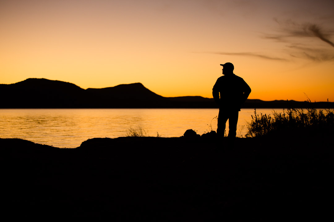 A silhouette portrait of a man standing on the shoreline of a large lake at sunset