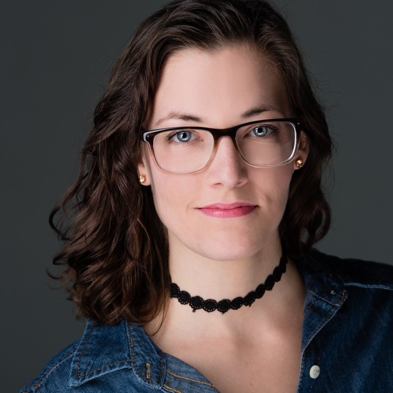 A young women with glasses and wavy brown hair beams with confidence in her headshot