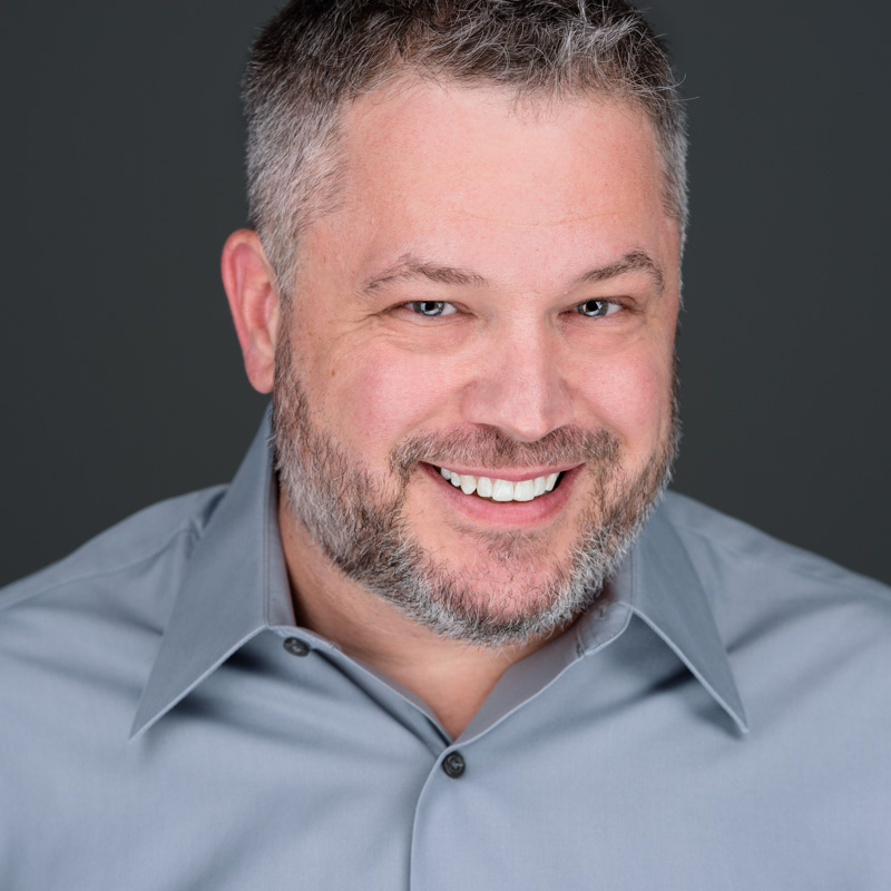 A business headshot of a smiling middle aged man with a short beard and gray hair